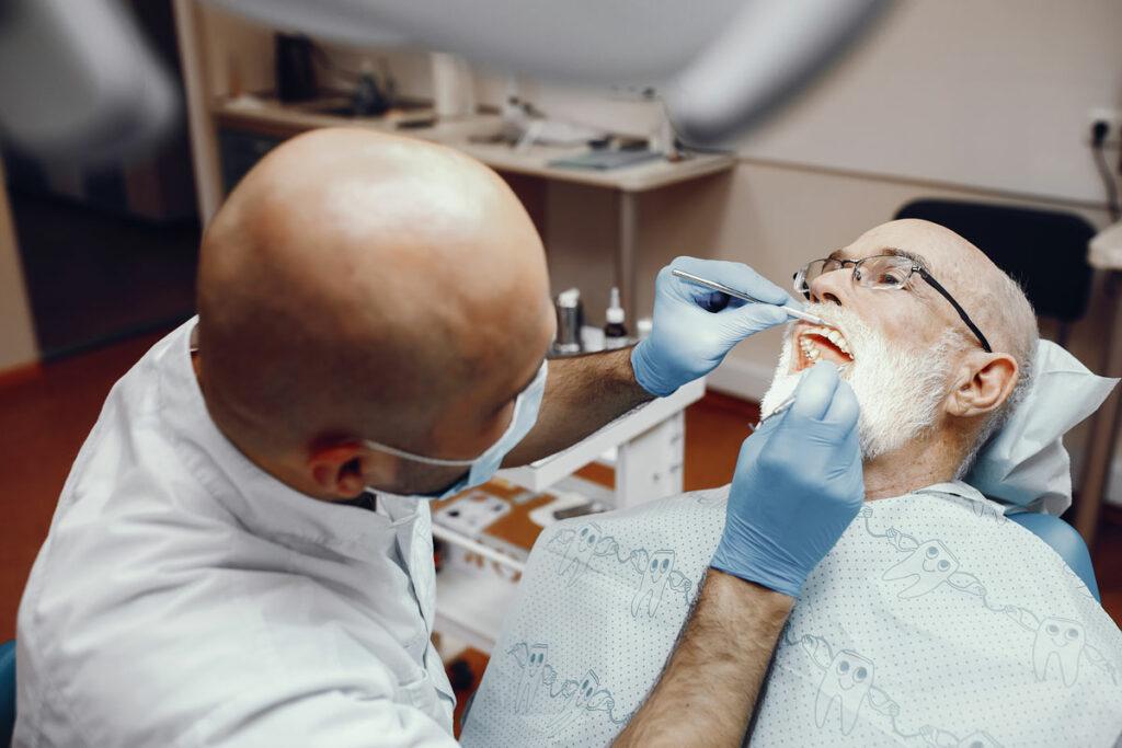 dentista che mette un impianto senza bucare l'osso a un vecchio signore