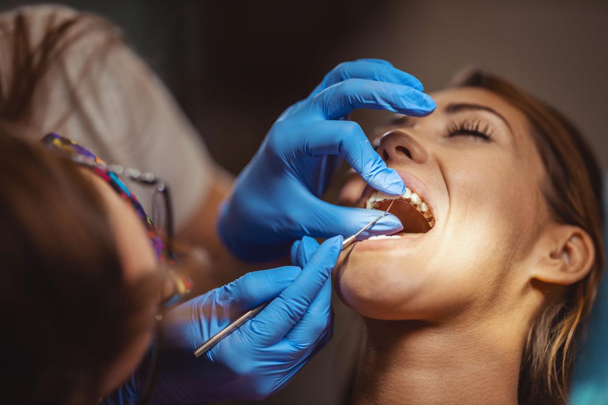 dentista che applica l'apparecchio linguale a una donna